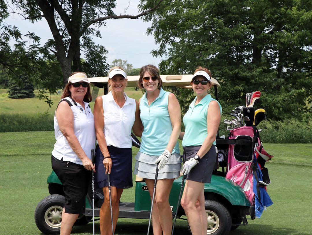 Four women at golf event.