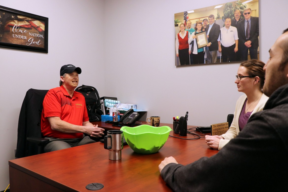 Image of Mark Plutschak visiting with Outlook associates in his office