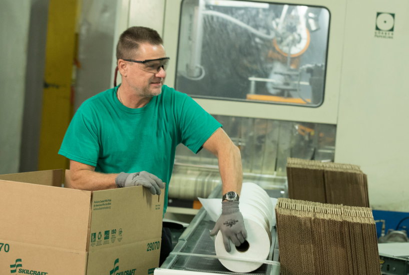 Image of blind associate packing boxes of paper towels.