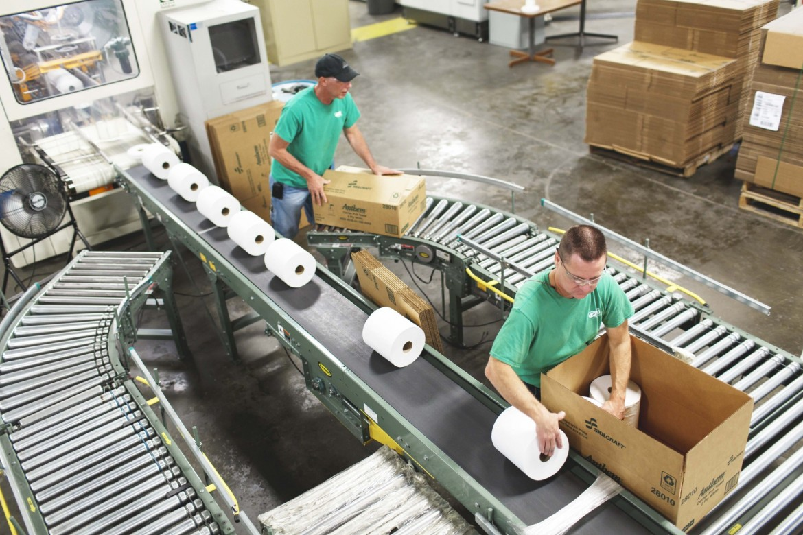 Image of visually impaired Outlook Associates packing toilet paper into boxes.